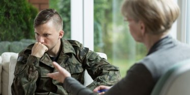 Troubled soldier with a therapist getting help for mental problems