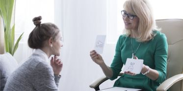 Young woman in therapy session with female educational therapist