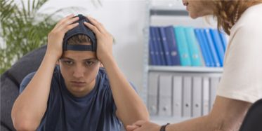 Young man in a backwards ballcap dealing with issues in therapy session