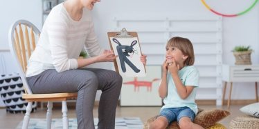 Little boy smiling at drawing of a rabbit during child psychology session