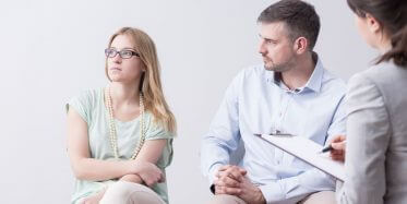 Wife ignoring her husband while struggling couple attends marriage therapy
