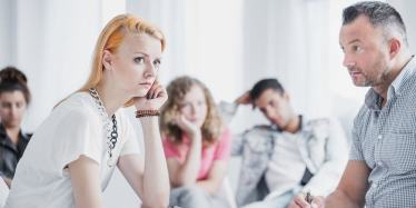 Young woman with red hair in anger group therapy session