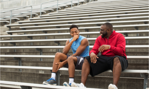 Two men laughing while sitting on stadium bleachers